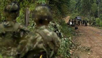 Soldados colombianos vigilan el traslado de los cuerpos sin vida de 11 militares luego del ataque a un grupo del Ejército por parte de la guerrilla de las Farc, el 15 de abril de 2015 en el departamento de Cauca, al suroccidente colombiano. (Crédito: LUIS ROBAYO/AFP/Getty Images)