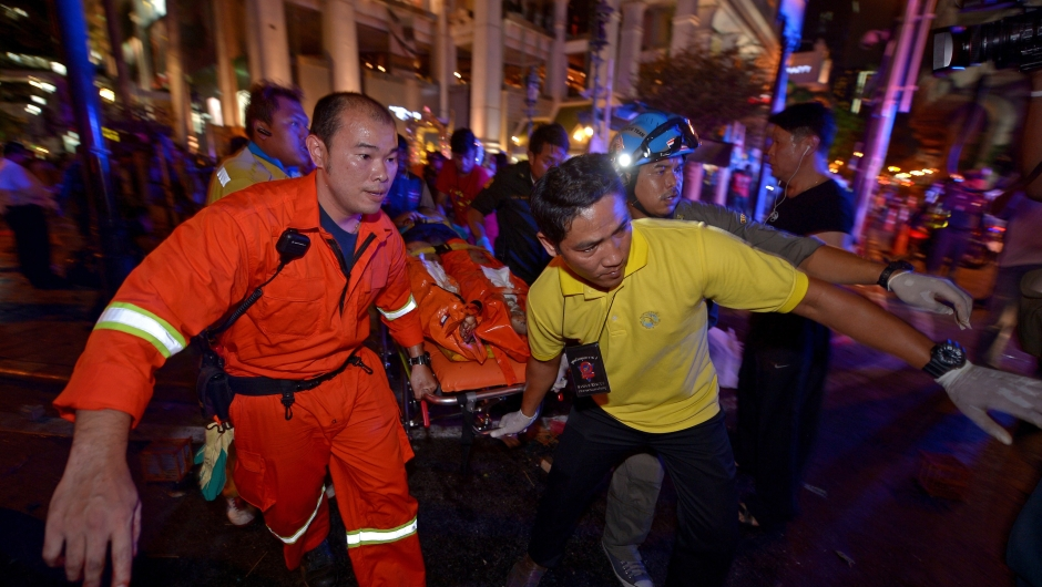 Thai rescue workers carry an injured person after a bomb exploded outside a religious shrine in central Bangkok late on August 17, 2015 killing at least 10 people and wounding scores more. Body parts were scattered across the street after the explosion outside the Erawan Shrine in the downtown Chidlom district of the Thai capital. AFP PHOTO / PORNCHAI KITTIWONGSAKUL (Photo credit should read PORNCHAI