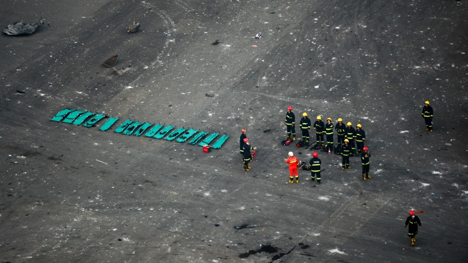 Rescuers are seen at the site of the massive explosions in Tianjin on August 13, 2015. Enormous explosions in a major Chinese port city killed at least 44 people and injured more than 500, state media reported on August 13, leaving a devastated industrial landscape of incinerated cars, toppled shipping containers and burnt-out buildings. CHINA OUT AFP PHOTO (Photo credit should read STR/AFP/Getty Images)