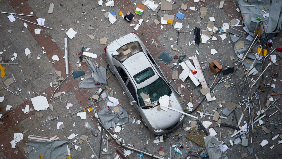 A damaged car is covered with shattered wall tiles and window parts at the site of the massive explosions in Tianjin on August 13, 2015. Enormous explosions in a major Chinese port city killed at least 44 people and injured more than 500, state media reported on August 13, leaving a devastated industrial landscape of incinerated cars, toppled shipping containers and burnt-out buildings. CHINA OUT AFP PHOTO (Photo credit should read STR/AFP/Getty Images)
