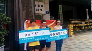 """Chen Qiuyan y sus amigos afuera de un tribunal en Cantón el 29 de julio de 2015. El cartel de la izquierda lee: """"Buscando justicia. Las personas gay pueden casarse en Estados Unidos, pero los libros de texto los estigmatizan en China""""."""