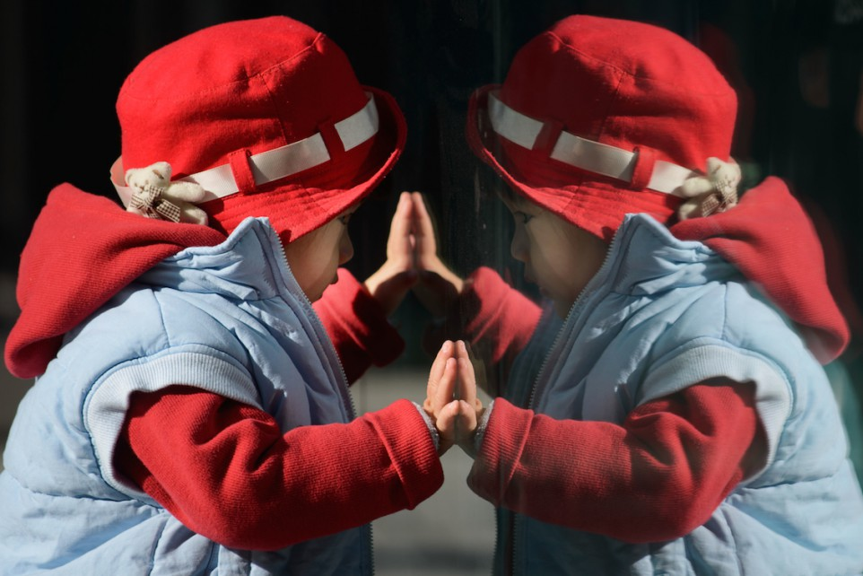 """A child looks at his reflection in a window in Beijing on November 17, 2013. On November 15 China's Communist rulers announced an easing of the country's controversial one-child policy as part of a raft of sweeping pledges including the abolition of its """"re-education"""" labour camps and loosening controls on the economy. AFP PHOTO / Ed Jones (Photo credit should read Ed Jones/AFP/Getty Images)"""