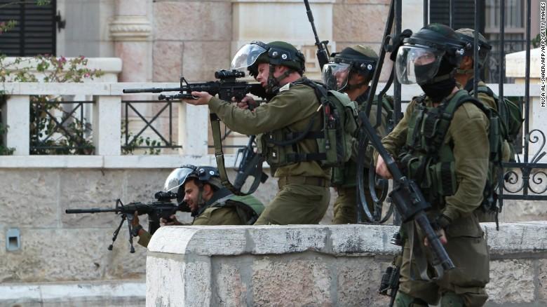 Soldados israelíes apuntan sus armas contra protestantes palestinos durante desórdenes en Belén el 12 de octubre.