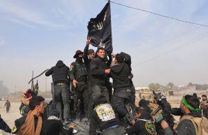 Militares de Iraq vapulean una bandera del grupo terrorista ISIS tras reconquistar la provincia de Diyala, a finales de enero del 2015. (Crédito: YOUNIS AL-BAYATI/AFP/Getty Images).