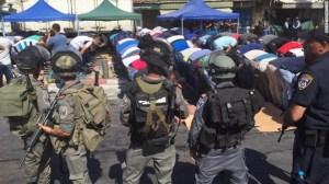 Fuerzas de seguridad Israelíes rodean fieles musulmanes durante la oración del Viernes.