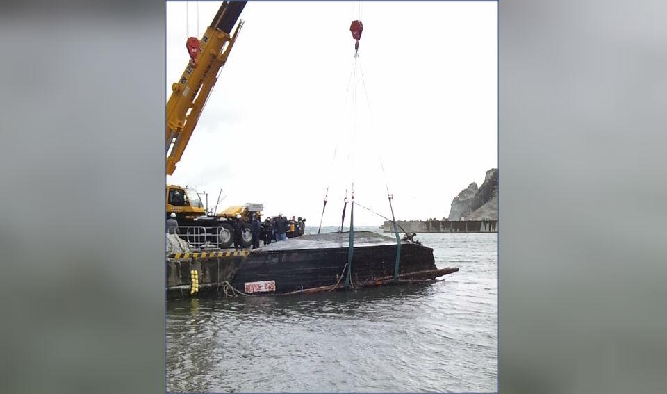 La guardia costera japonesa saca al barco de madera del agua.