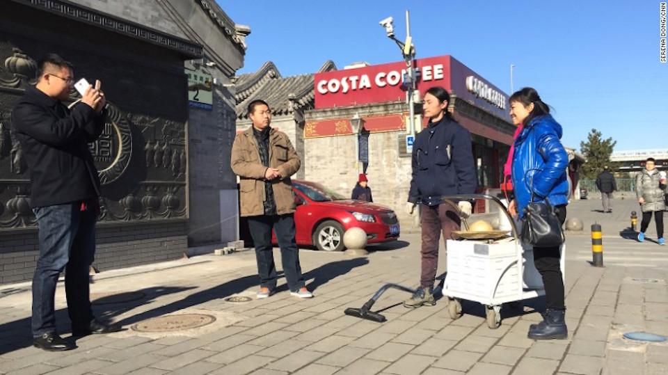 Brother Nut de China se toma fotos con sus admiradores en el pavimento.