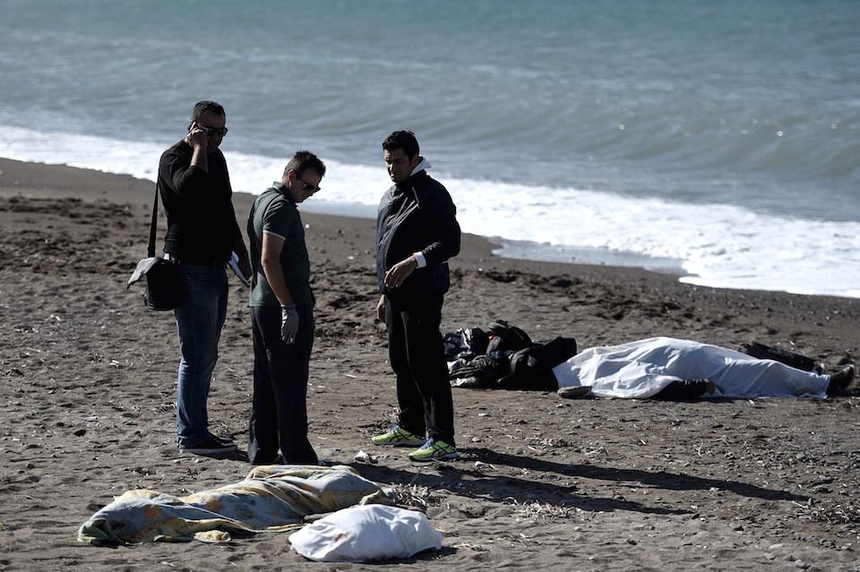 Oficiales de policía cerca a los cuerpos sin vida de tres niños y un hombre que se ahogaron al intentar cruzar el mar Egeo desde Turquía,hacia la isla griega de Lesbos, el 30 de octubre de 2015. (Crédito: ARIS MESSINIS/AFP/Getty Images)