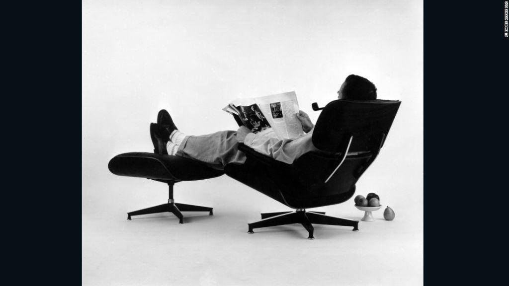 Charles Eames en la silla y otomana de madera contrachapada. Fotografía para un anuncio publicitario, 1956.