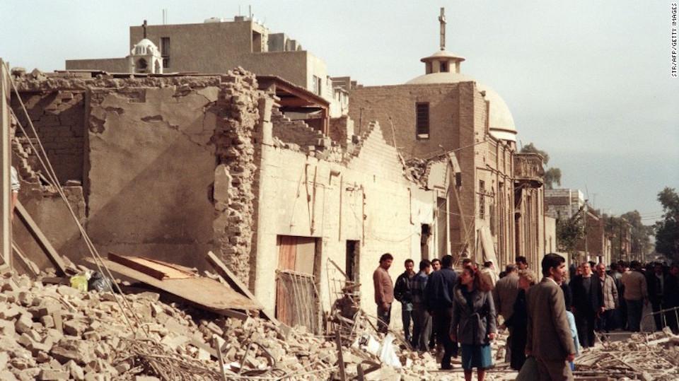 Una foto tomada el 16 de febrero de 1991 muestra a trabajadores civiles de defensa iraquíes y a civiles que veían el daño cerca de una iglesia cristiana, ocasionado por una redada de bombardeos por parte de los aliados en Bagdad.