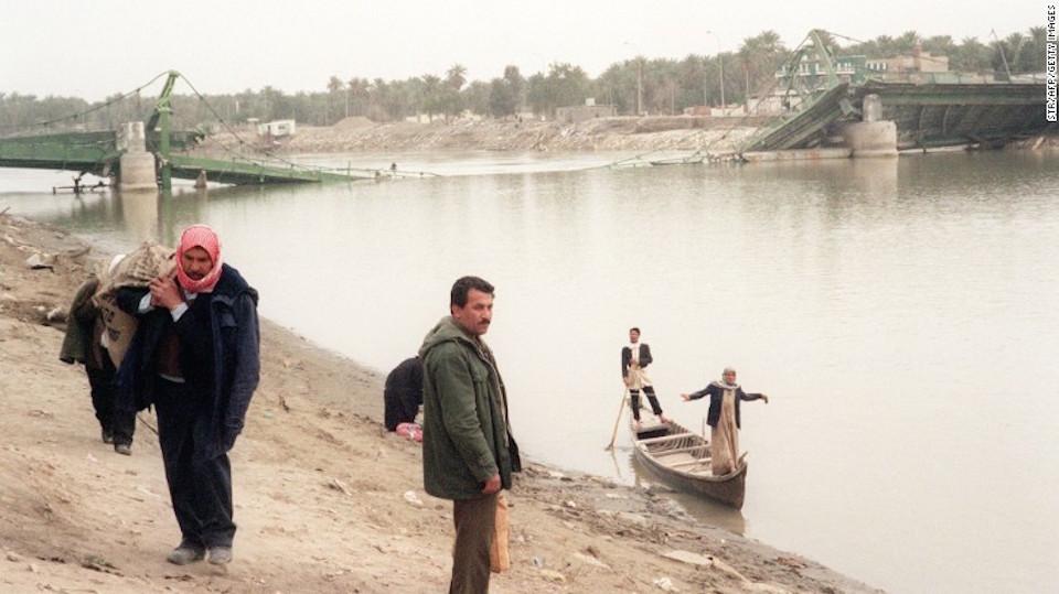 Habitantes de Samawah, a 280 kilómetros al sur de Bagdad, aparecen en imágenes utilizando pequeños botes para cruzar el río Éufrates el 17 de febrero de 1991, cuando tres puentes al centro de la ciudad fueron destruidos en las redadas aéreas por parte de los aliados en Iraq.