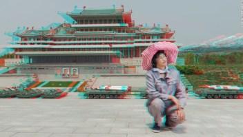 """Ri Gyong Sun, de 45 años de edad, en la sección de Mantenimiento de Historia Antigua en el Parque Folclórico de Pyonyang – """"Este retrato fue tomado en un parque en Pyonyang que tiene sitios [famosos], pero en miniatura. Esta señora se encarga del follaje de la zona. Le pedí que se pusiera de pie junto a la biblioteca en miniatura. Pero ella dijo que no podía tomarse una foto en donde ella se viera más alta que los líderes en la foto, así que le pregunté si podía arrodillarse y ella accedió""""."""