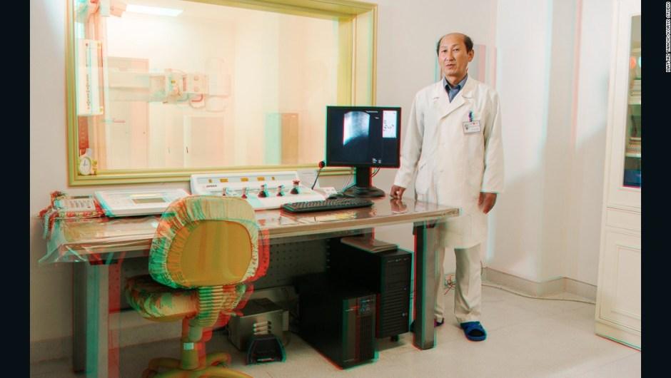 """Sin Sae Chol, de 57 años de edad, médico de rayos X en el Centro de Oncología, Hospital de Maternidad y Mamografías – """"Este fue uno de los lugares que era realmente estereotípico de Corea del Norte y el único lugar donde sentí que pensaban que éramos idiotas. Era completamente nuevo, de mármol, enormes pantallas plasma, todo el mundo allí era joven y hermoso, todas las máquinas, todo era completamente nuevo y sorprendente. Esto realmente se tendía frente a tu rostro... Pero luego de caminar a través de toda la falsedad de este hospital, me las arreglé para conocer a un personaje interesante. La habitación estaba muy bien decorada con cosas hechas en casa, así que tomé un retrato de él""""."""