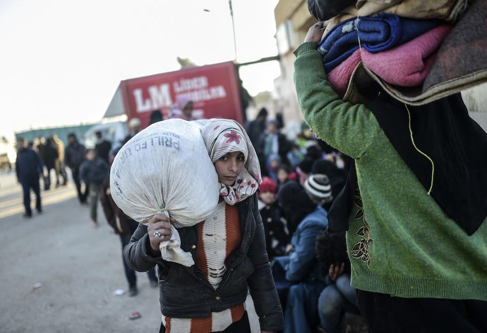 Una joven refugiada siria se apresura a llegar a la zona fronteriza con Turquía. Cerca de 40.000 mil personas han salido de Aleppo en días recientes. (Crédito: BULENT KILIC/AFP/Getty Images).