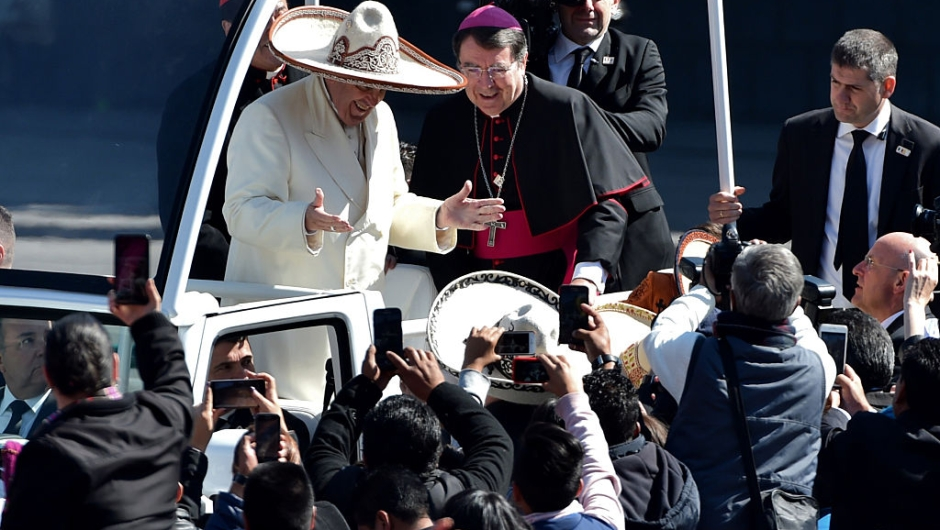 Pope Francis receives a traditional Mexican sombrero and greets people on his ride in the popemobile to the Zocalo in Mexico City on February 13, 2016. AFP PHOTO/ Mario Vazquez / AFP / MARIO VAZQUEZ (Photo credit should read MARIO VAZQUEZ/AFP/Getty Images)