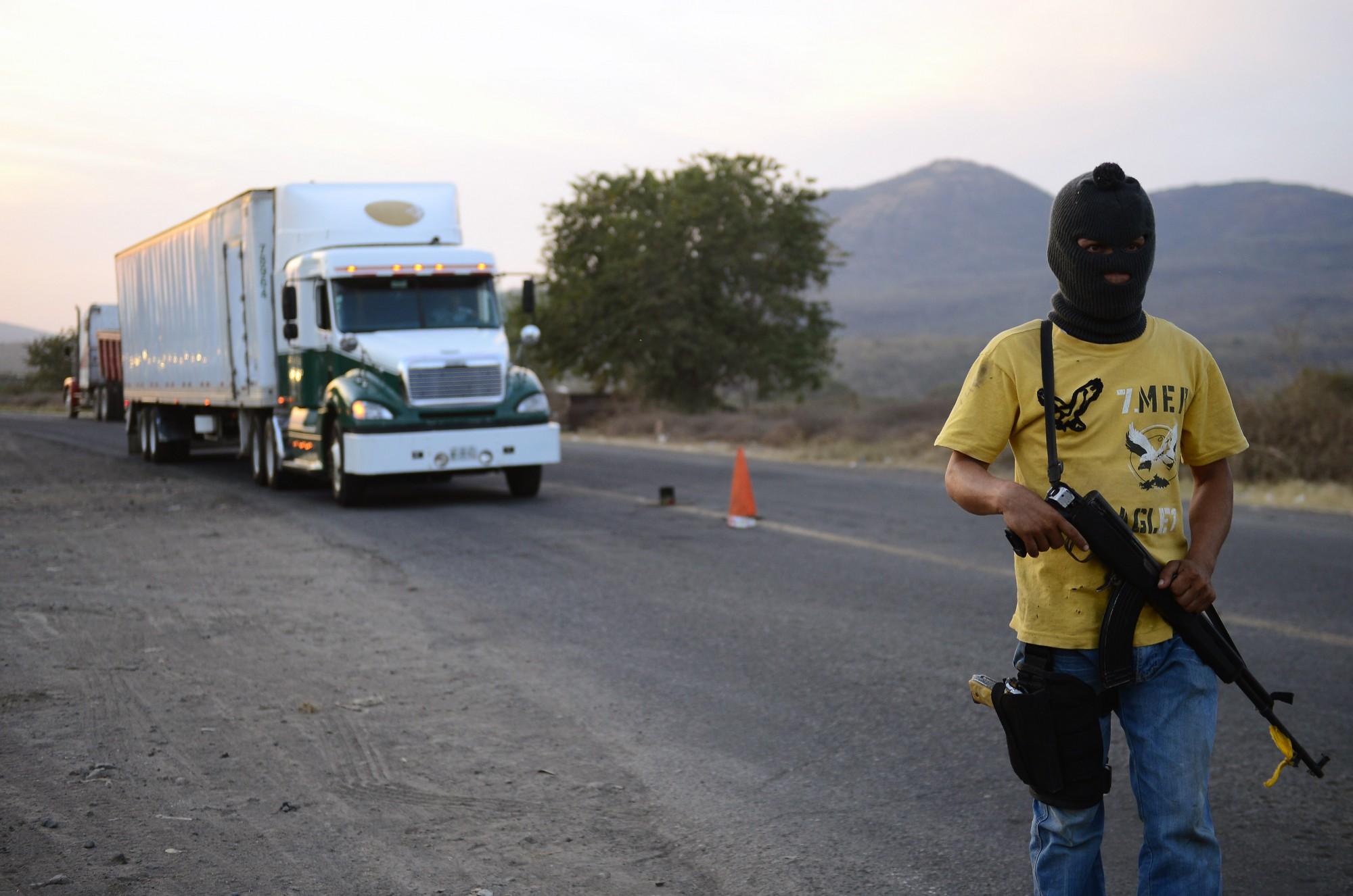 Un miembro de un grupo de autodefensa patrulla una carretera entre Tepalcatepec y Apatzingán, en el estado de Michoacán. Grupos de civiles tomaron las armas en 2014 en respuesta a la violencia causada por los cárteles de la droga. (Crédito: Alfredo Estrella/AFP/Getty Images)