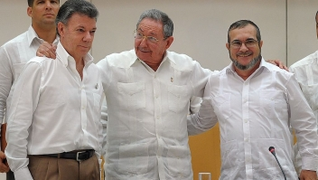 """PAZ RECONCILIACIÓN COLOMBIA Cuban President Raul Castro (C) embraces Colombian President Juan Manuel Santos (L) and the head of the FARC guerrilla Timoleon Jimenez, aka Timochenko (R), during a meeting in Havana on September 23, 2015. The Colombian government and FARC rebels announced a key breakthrough in their nearly three-year peace talks Wednesday with the signing of a deal on justice for crimes committed during the five-decade conflict. The deal includes the creation of special courts and a broad amnesty, though this will not cover """"crimes against humanity, serious war crimes"""" and other offenses including kidnappings, extrajudicial executions and sexual abuse, said officials from Cuba and Norway, the guarantors in the talks. AFP PHOTO / Yamil Lage (Photo credit should read YAMIL LAGE/AFP/Getty Images)"""