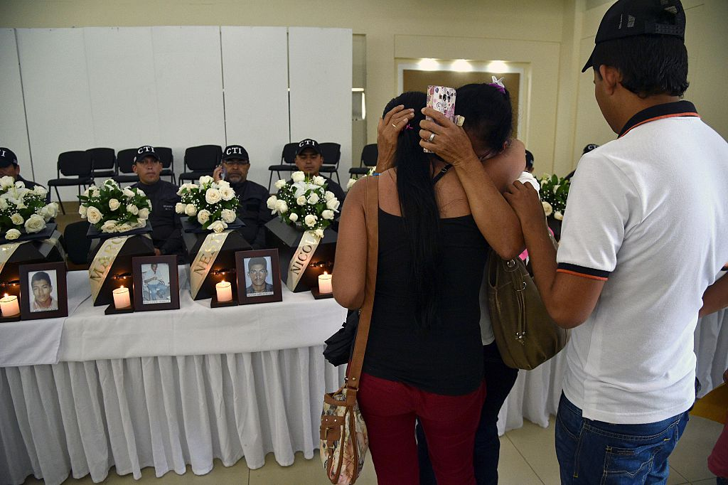 PAZ RECONCILIACIÓN COLOMBIA Relatives of a victim of the armed conflict in Colombia cry during a ceremony marking the dignified return of the remains, in Villavicencio, Meta department, on December 17, 2015. Relatives of twenty nine victims received the remains of their loved ones, recently identified after being found in common graves in five municipal cemeteries of the Meta and Guaviare departments in Colombia, in the framework of the agreement between the country's government and the FARC guerrilla. AFP PHOTO / GUILLERMO LEGARIA / AFP / GUILLERMO LEGARIA (Photo credit should read GUILLERMO LEGARIA/AFP/Getty Images)