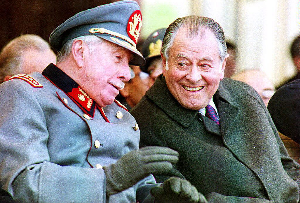 SANTIAGO, CHILE: Former Chilean President Gen. Augusto Pinochet (L), commander of the armed forces, talks with President Patricio Aylwin 09 July 1993 during the swearing-in of some 1,000 concripts into the army in Santiago, Chile. Both leaders are seeking a solution to demands for justice against 230 servcicemen accused of human rights abuses. (Photo credit should read CRIS BOURONCLE/AFP/Getty Images)