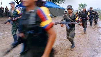 PAZ RECONCILIACIÓN FARC SAN VICENTE, COLOMBIA - APRIL 29: Guerrillas of the Revolutionary Armed Forces of Columbia retreat from San Vicente del Caguan, after the launcing of the victory party of Bolivia, 29 April 2000. Guerrilleros de las Fuerzas Armadas Revolucionarias de Colombia FARC se retiran de San Vicente del Caguan, tras el lanzamiento del Partido Bolivariano, el 29 de abril de 2000. El Partido Bolivariano actuara desde la clandestinidad para proteger a sus integrantes de los grupos paramilitares, fue fundado en medio del rechazo militar y politico por el anuncio previo de que sera un partido para la guerra. (Photo credit should read WILIAM MARTINEZ/AFP/Getty Images)