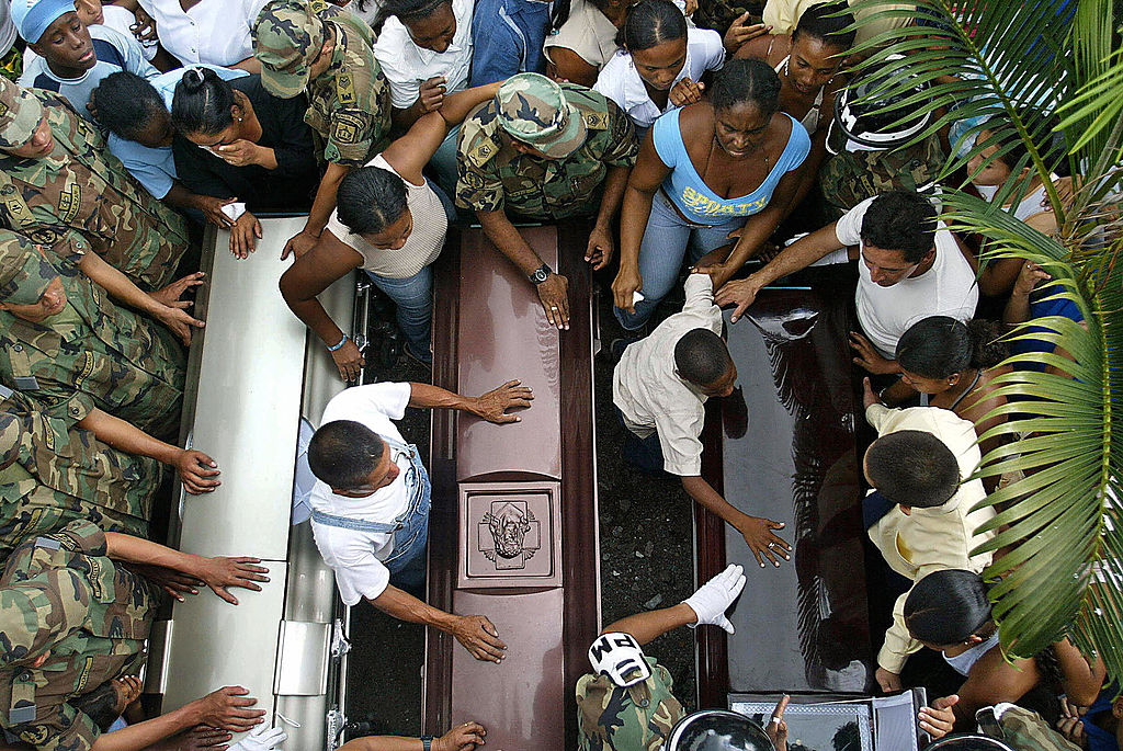 PAZ RECONCILIACIÓN FARC CAREPA, COLOMBIA: Relatives moan next to the coffins of soldiers Luis Adan Hoyos, Luis Alberto Benites and Emilon Rodriguez, during their wake in Carepa, Colombia, 11 February 2005. At least 19 soldiers were murdered during fightings against the Colombian Revolutionary Armed Forces (FARC) guerrillas. AFP PHOTO/Gerardo GOMEZ (Photo credit should read GERARDO GOMEZ/AFP/Getty Images)