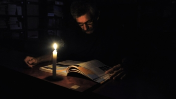 A man reads with a candle's light during a power cut in the border state of San Cristobal, Venezuela, 600 km west of Caracas on April 25, 2016. Recession-hit Venezuela will turn off the electricity supply in its 10 most populous states for four hours a day for 40 days to deal with a severe power shortage, the government said Thursday. / AFP / GEORGE CASTELLANOS (Photo credit should read GEORGE CASTELLANOS/AFP/Getty Images)