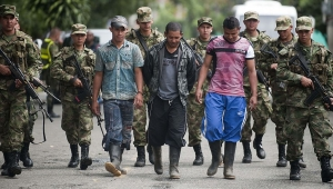 Three demobilized fighters of the 36th Column of the FARC leftist guerrillas are escorted by Colombian soldiers during a press conference on September 20, 2012 in Medellin, Antioquia department, Colombia. Seven FARC members were demobilized after surrendering their weapons. AFP PHOTO/Raul ARBOLEDA (Photo credit should read RAUL ARBOLEDA/AFP/GettyImages)