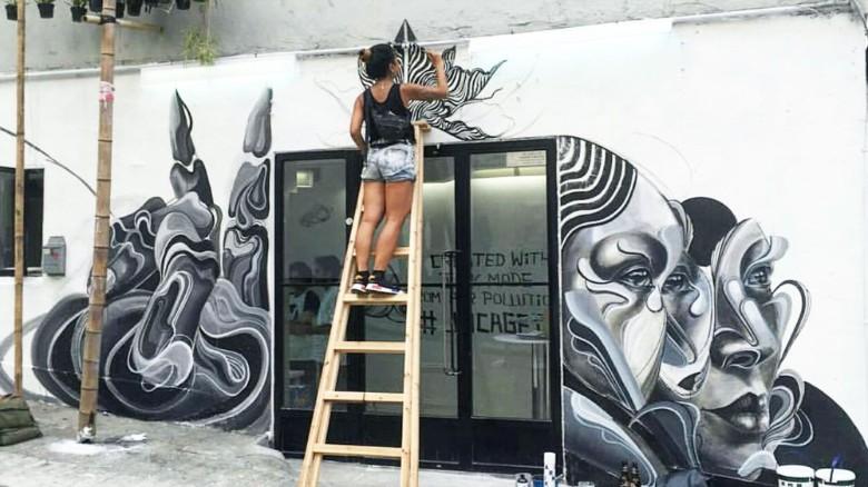 La artista Caratoes pinta un mural con Air Ink.