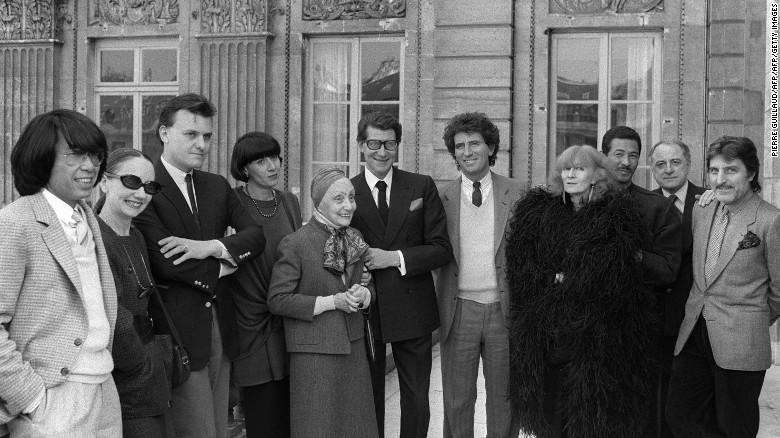Sonia Rykiel (con abrigo de plumas negras) posa con el Ministro de Cultura francés Jack Lang (séptimo de izquierda a derecha) y sus contemporáneos de la moda en París en 1984.