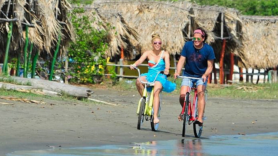 """Colombian singers Shakira (L) and Carlos Vives (R) ride bikes during the recording of the video for the song """"La Bicicleta"""" in Puerto Velero, Barranquilla, Atlantico department on May 19, 2016. / AFP / JOSE TORRES (Photo credit should read JOSE TORRES/AFP/Getty Images)"""