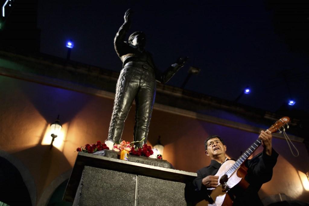 Un músico interpreta una canción delante de la imagen del cantante y compositor mexicano Juan Gabriel en la Plaza Garibaldi, el 28 de agosto de 2016, en la Ciudad de México. Crédito: YURI CORTEZ / AFP / Getty Images.