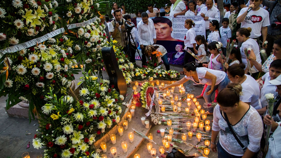 """Candles and flowers are seen in an altar at the feet of a statue of Mexican composer and singer Alberto Aguilera, known as """"Juan Gabriel"""" in Paracuaro, Michoacan state, Mexico on August 29, 2016. Mexico and the music world on Monday mourned the death of legendary singer Juan Gabriel, who touched millions with wrenching ballads of love and loneliness as he rose from the rough streets of Ciudad Juarez to a world stage. / AFP / ENRIQUE CASTRO (Photo credit should read ENRIQUE CASTRO/AFP/Getty Images)"""