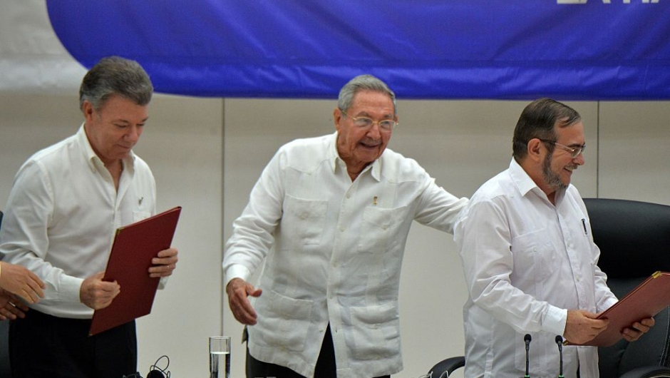 "Colombia's President Juan Manuel Santos (L), Cuban President Raul Castro (C) and Timoleon Jimenez, aka ""Timochenko"" (R), head of the FARC leftist guerrilla, during the signing of the ceasefire in Havana on June 23, 2016. Colombia's government and the FARC guerrilla force signed a definitive ceasefire Thursday, taking one of the last crucial steps toward ending Latin America's longest civil war. / AFP / ADALBERTO ROQUE (Photo credit should read ADALBERTO ROQUE/AFP/Getty Images)"