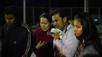 Un grupo de personas llora mientras observa cómo los rescatistas se llevan el cuerpo de uno de sus familiares que falleció en los deslizamientos en Guatemala. (JOHAN ORDONEZ/AFP/Getty Images)