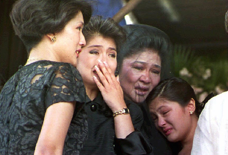 BATAC, PHILIPPINES: Former first lady Imelda Marcos (2nd R) and her children Irene Araneta (L), Imee Manotoc (C) and adopted daughter Aimee (R) weep 09 September 1993 during a public eulogy for Ferdinand Marcos in Batac, Philippines. Marcos' remains arrived 07 September in his northern Philippine hometown for final burial. (Photo credit should read ROMEO GACAD/AFP/Getty Images)