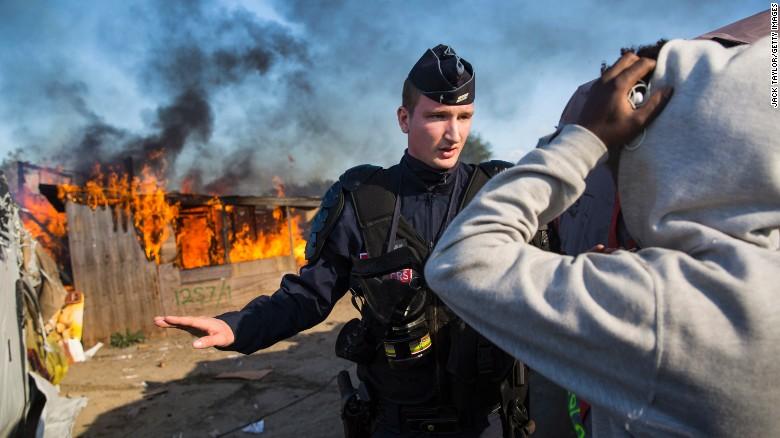 Un policía cuida el lugar luego de que inmigrantes quemaran un refugio mientras las autoridades desmantelaban el campamento.