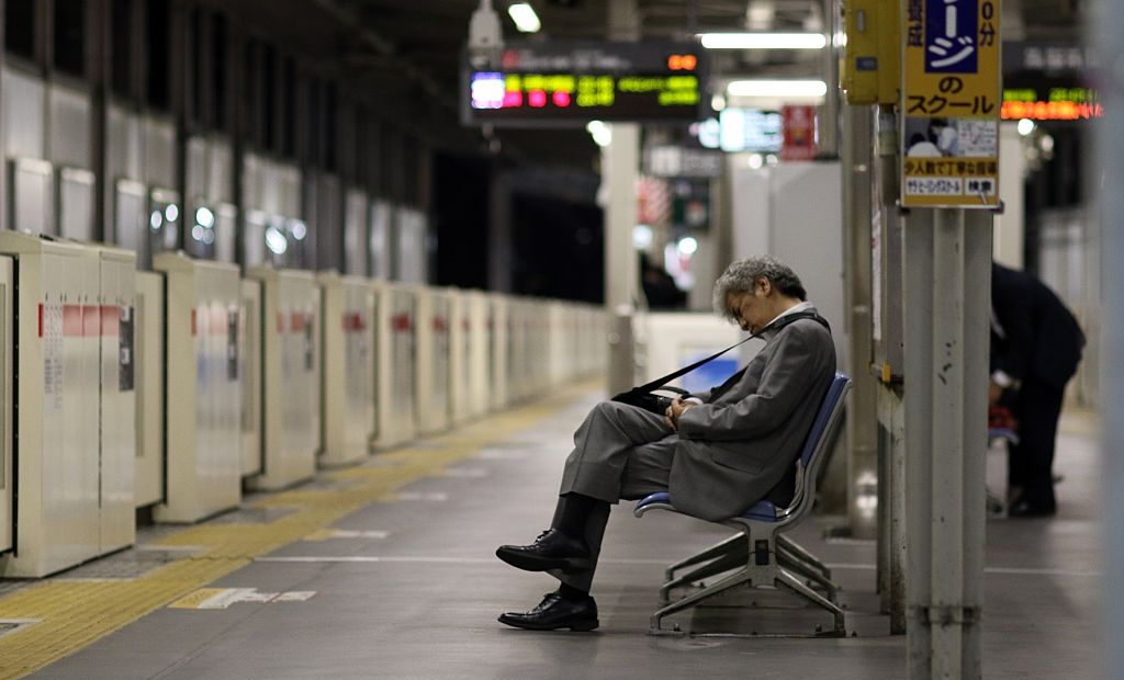 "TO GO WITH ""JAPAN-LABOUR-LIFESTYLE-ECONOMY"" BY NATSUKO FUKUE This picture taken on May 22, 2015 shows a businessman sleeping on a bench at a Tokyo train station. Japan's push to take away overtime from high-paid workers has critics warning it will aggravate a problem synonymous with the country's notoriously long working hours -- karoshi, or death from overwork. AFP PHOTO / Yoshikazu TSUNO (Photo credit should read YOSHIKAZU TSUNO/AFP/Getty Images)"