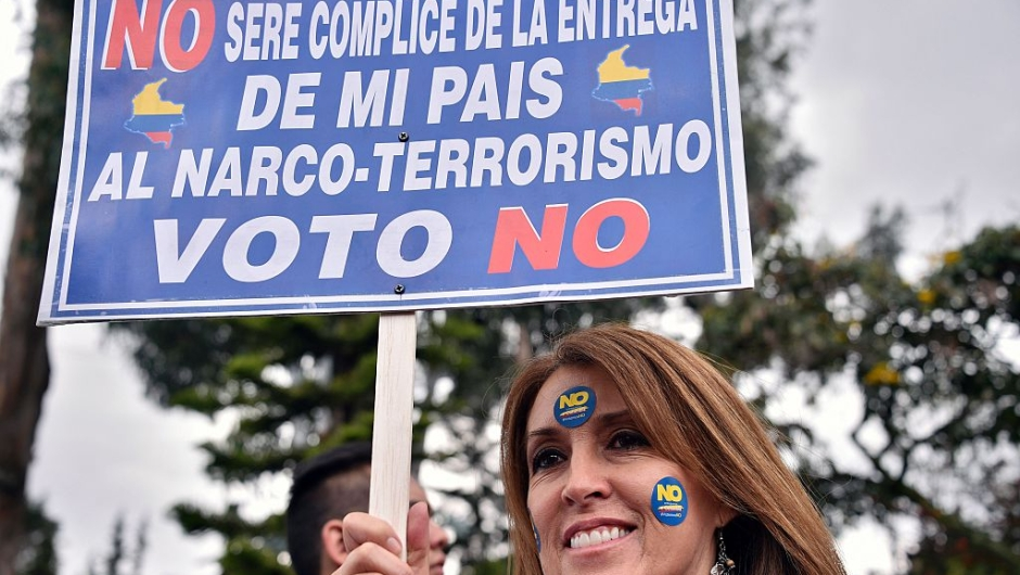 "A woman holds a sign reading ""I won't be accomplice of the handing of my country to drug-terrorism. I vote No"" during a motorcade ahead of Sunday referendum in Bogota, on October 1, 2016. Colombians will vote a referendum Sunday on whether to ratify a historic peace accord to end the 52-year war between the state and the communist FARC rebels. The accord will effectively end what is seen as the last major armed conflict in the Western Hemisphere. The war has killed hundreds of thousands of people and displaced millions. / AFP / GUILLERMO LEGARIA (Photo credit should read GUILLERMO LEGARIA/AFP/Getty Images)"