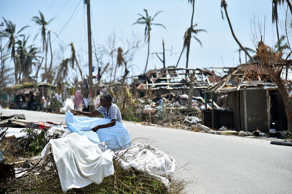 "A woman displays her clothes in front of her destroyed house in Les Cayes, Haiti on October 10, 2016, following the passage of Hurricane Matthew. Haiti faces a humanitarian crisis that requires a ""massive response"" from the international community, the United Nations chief said , with at least 1.4 million people needing emergency aid following last week's battering by Hurricane Matthew. / AFP / HECTOR RETAMAL (Photo credit should read HECTOR RETAMAL/AFP/Getty Images)"