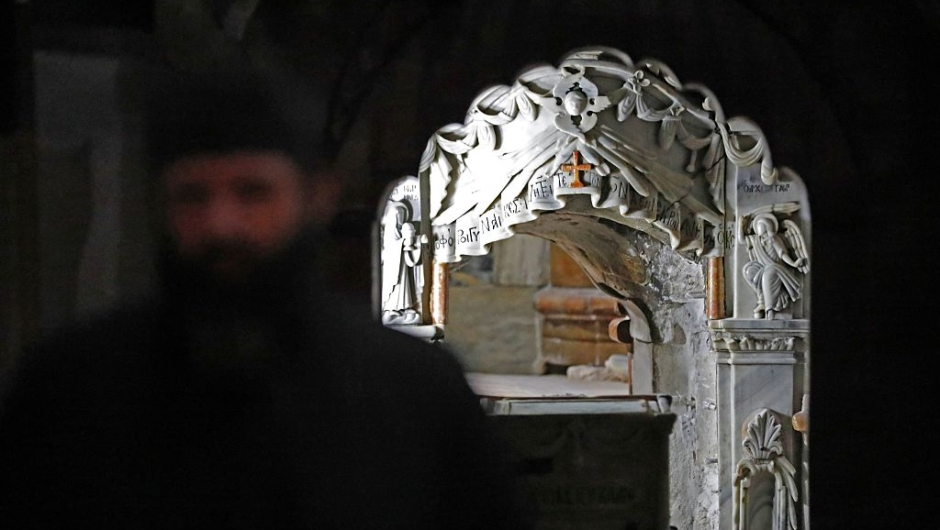 A Greek Orthodox priest stands in front of the Tomb of Jesus at the Church of the Holy Sepulchre in Jerusalem's Old City on October 28, 2016. The tomb where Jesus is said to have been buried before his resurrection, is to undergo major restoration. The restoration entrusted to a Greek team, is expected to be completed in early 2017 and the site will remain open to visitors in the meantime. / AFP / THOMAS COEX (Photo credit should read THOMAS COEX/AFP/Getty Images)
