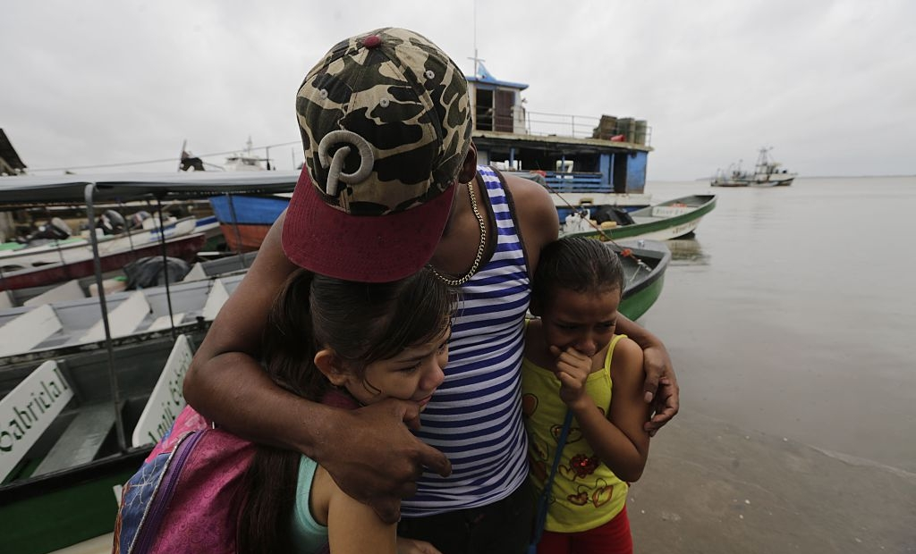 "TOPSHOT - Two children seek cover under the embrace of their father before Hurricane Otto arrives in Bluefields, Nicaragua on November 23, 2016. A Caribbean storm verging on a hurricane spun towards the coasts of Costa Rica and Nicaragua on Wednesday, prompting evacuations and red alerts ahead of ""life-threatening"" flash flooding. / AFP / INTI OCON (Photo credit should read INTI OCON/AFP/Getty Images)"