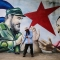 TOPSHOT - A municipal worker sweeps the floor in front of a mural depicting Cuban revolutionary leader Fidel Castro (L) and Nicaraguan President Daniel Ortega at Cuba square in Managua on November 26, 2016, the day after Castro died. Cuban revolutionary leader Fidel Castro has died aged 90, prompting mixed grief and joy Saturday along with international tributes for the man whose iron-fisted rule defied the United States for half a century. / AFP / INTI OCON (Photo credit should read INTI OCON/AFP/Getty Images)