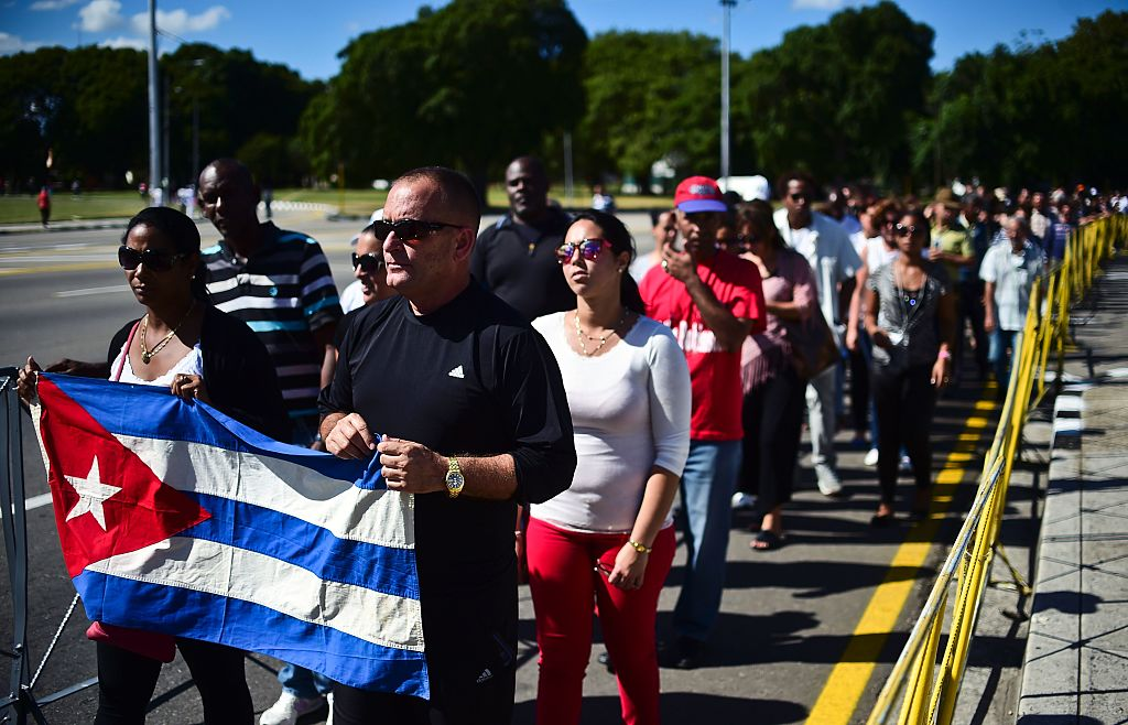 People holding a Cuban national flag queue to enter Jose Marti's memorial to pay their last respects to Cuban revolutionary icon Fidel Castro at Revolution Square in Havana, on November 28, 2016. A titan of the 20th century who beat the odds to endure into the 21st, Castro died late Friday after surviving 11 US administrations and hundreds of assassination attempts. No cause of death was given. Castro's ashes will go on a four-day island-wide procession starting Wednesday before being buried in the southeastern city of Santiago de Cuba on December 4. / AFP / RONALDO SCHEMIDT (Photo credit should read RONALDO SCHEMIDT/AFP/Getty Images)
