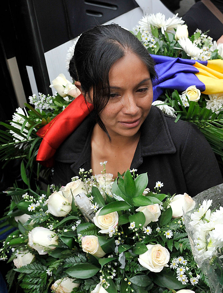 The mother of Yuliana - a seven-year-old girl who was raped, tortured and murdered - holds white flowers and a Colombian flag after a mass held in the victim's honour at the Santa Teresita church in Bogota, Colombia, on December 7, 2016. A seven-year-old girl was raped, tortured and murdered in Bogota this weekend, allegedly by a 38-year-old man who kidnapped the girl from her low-income neighborhood on the east side of the city and took her to a luxury apartment belonging to his family, the police said. The girl's body was found on the scene, showing signs of torture and sexual abuse. / AFP / GUILLERMO LEGARIA (Photo credit should read GUILLERMO LEGARIA/AFP/Getty Images)