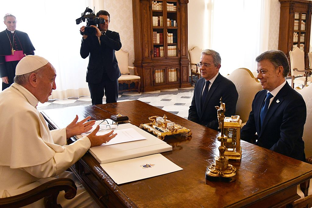 Pope Francis (l) speaks with Colombian president Juan Manuel Santos (R) and former president Alvaro Uribe prior to a meeting, on January 16, 2016 at the Vatican. / AFP / POOL / VINCENZO PINTO (Photo credit should read VINCENZO PINTO/AFP/Getty Images)