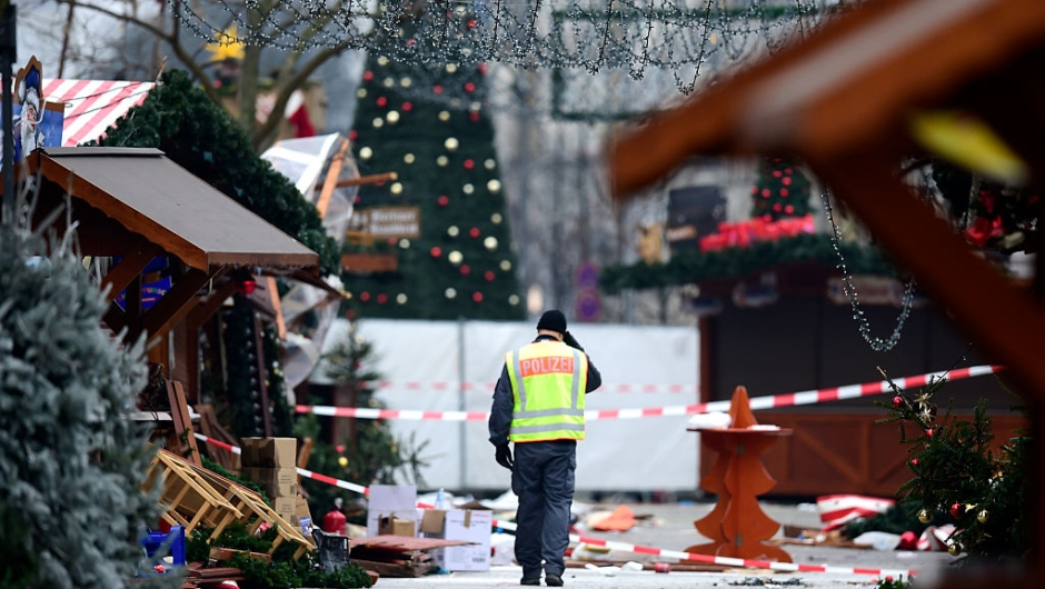 """A policeman walks at the Christmas market near the Kaiser-Wilhelm-Gedaechtniskirche (Kaiser Wilhelm Memorial Church), the day after a terror attack, in central Berlin, on December 20, 2016. German police said they were treating as """"a probable terrorist attack"""" the killing of 12 people when the speeding lorry cut a bloody swath through the packed Berlin Christmas market. / AFP / Tobias SCHWARZ (Photo credit should read TOBIAS SCHWARZ/AFP/Getty Images)"""