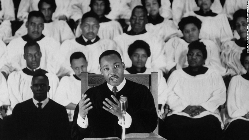 Civil Rights activist Rev. Dr. Martin Luther King Jr. standing at pulpit delivering his sermon as a white-robed choir listens in the bkgd. at Ebenezer Baptist Church. (Photo by Donald Uhrbrock//Time Life Pictures/Getty Images)