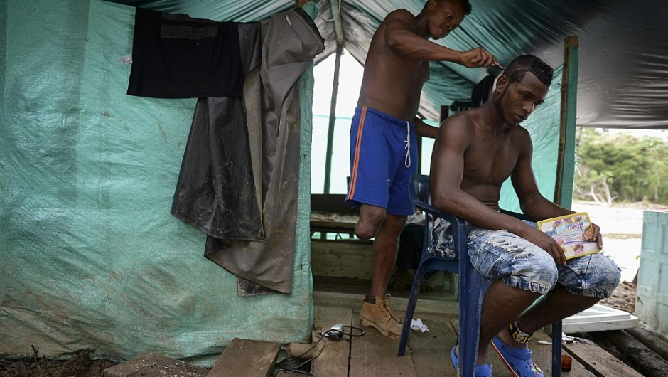 TOPSHOT - A FARC guerillas member has his hair cut at the 34 Alberto Martinez camp front just days before their demobilization to the final concentration zones, in Vegaez municipality, Antioquia department, Colombia on December 30, 2016. The Colombian government signed a final peace agreement with the FARC guerrilla on November 26 to be implemented within the next six months, during which FARC members will give up their weapons and start their transition to be reintegrated into society. / AFP / STR / RAUL ARBOLEDA (Photo credit should read RAUL ARBOLEDA/AFP/Getty Images)