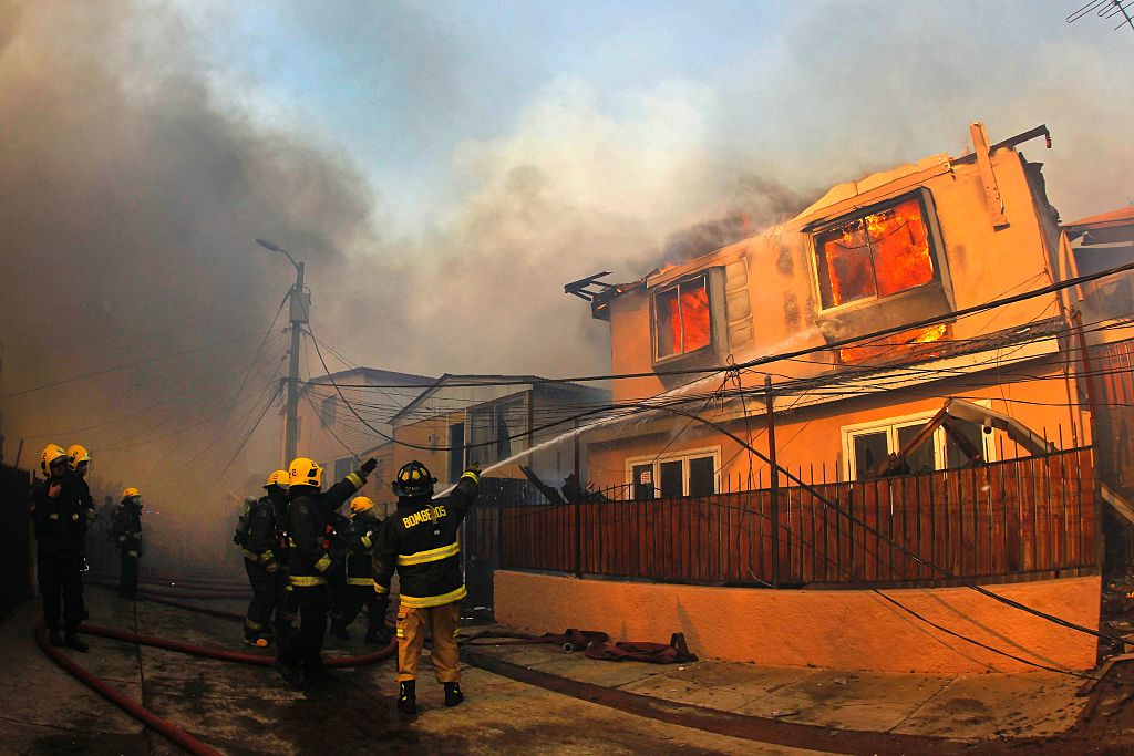 Firefighters work to extinguish the flames from a house in Valparaiso, Chile, on January 02, 2017 as the fire threatens to reach the city's port, authorities have declared a red alert in the area. / AFP / ATON CHILE / Sebastián CISTERNAS / (Photo credit should read SEBASTIAN CISTERNAS/AFP/Getty Images)