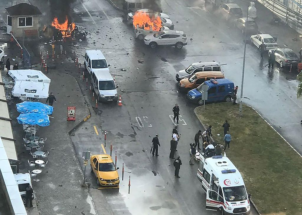 Cars burn in the street at the site of an explosion in front of the courthouse in Izmir on January 5, 2017. A car bomb exploded outside a courthouse in the western Turkish city of Izmir, wounding at least 10 people and sparking clashes in which at least two 'terrorists' were killed, officials and reports said.Several ambulances were rushed to the scene after the blast outside the prosecutors and judges' entrance to the court in the usually peaceful city on the Aegean Sea, the channel said. / AFP / DOGAN NEWS AGENCY / DHA (Photo credit should read DHA/AFP/Getty Images)